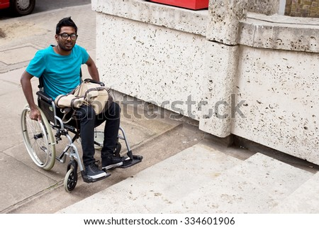 young man in a wheelchair at the bottom of steps - stock photo