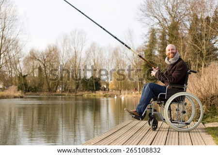 young man in a wheelchair fishing - stock photo