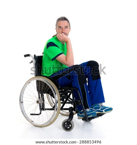 young man in a wheelchair in front of white background is sad - stock photo
