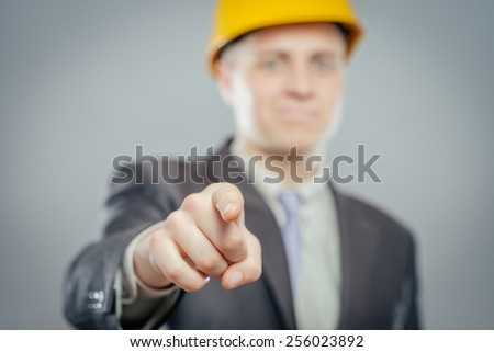 young  man in a yellow helmet pointing at someone gesture with finger - stock photo