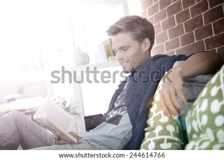 Young man in apartment reading book - stock photo