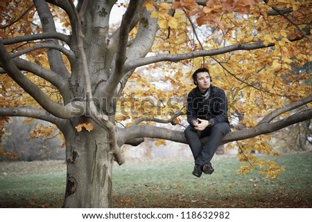 Young man in autumn park - stock photo