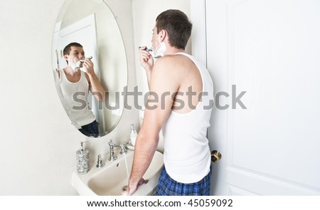 Young man in bathroom looking in the mirror and shaving. Horizontal shot. - stock photo