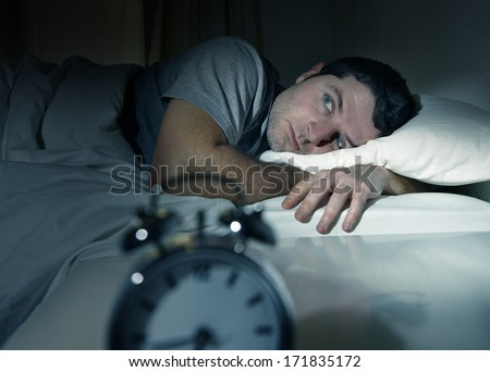 young man in bed with eyes opened suffering insomnia and sleep disorder thinking about his problem - stock photo