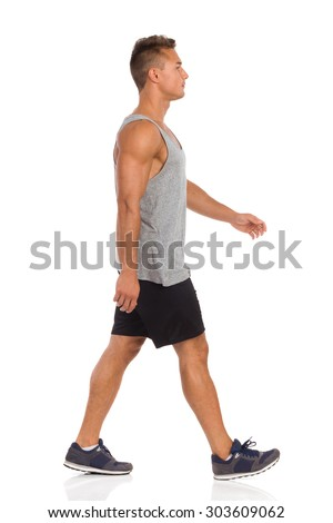 Young man in beige shorts, blue shirt and sneakers walking. Side view. Full length studio shot isolated on white. - stock photo