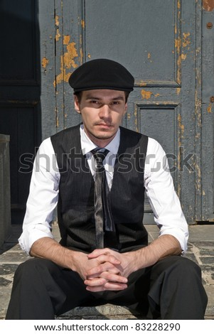 young man in black cap in vintage style against the background old door - stock photo