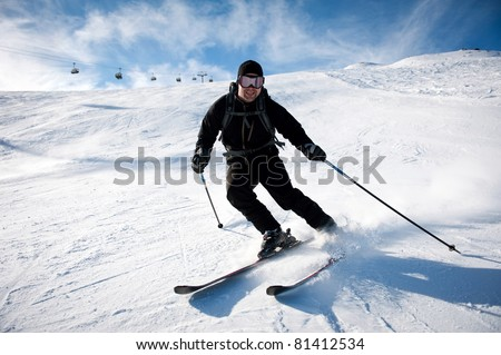 young man in black clothing skiing on mountain slope at ski resort - stock photo