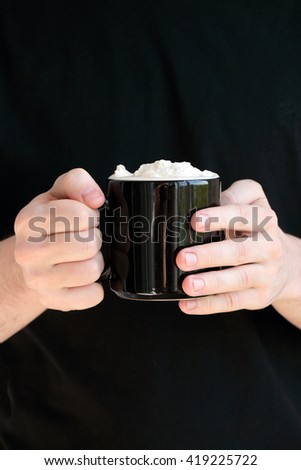 Young man in black holding a black cup (mug) of coffee with whipped cream - stock photo