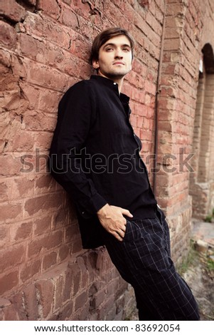 young man in black shirt and pants leaning against the wall - stock photo