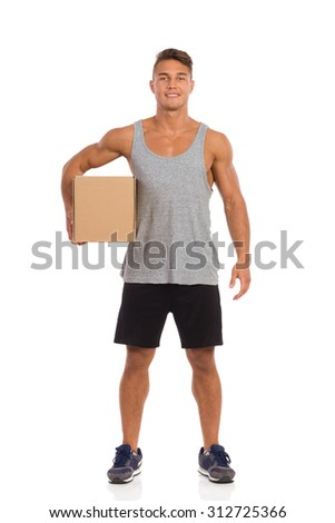 Young man in black shorts and sneakers standing and holding carton box under his arm. Front view full length studio shot isolated on white.