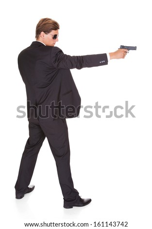 Young Man In Black Suit Aiming With A Gun On White Background