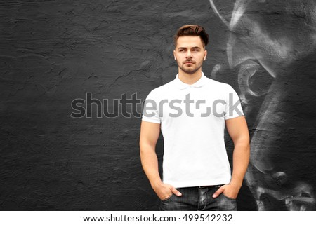 Young man in blank polo shirt against graffiti wall