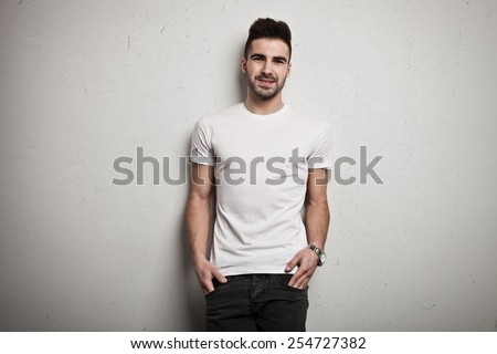 Young man in blank t-shirt, white grunge wall background