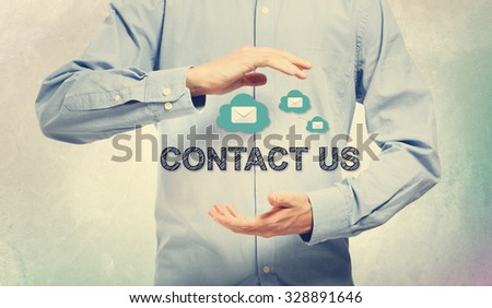 Young man in blue shirt holding Contact Us - stock photo