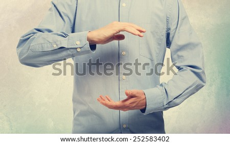 Young man in blue shirt holding something in his arms - stock photo