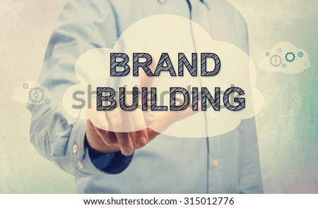Young man in blue shirt pointing at BRAND BUILDING - stock photo