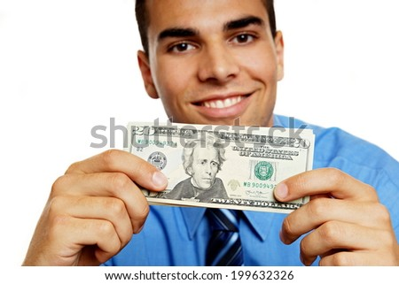 Young man in blue shirt shows you money, focus is on money - stock photo