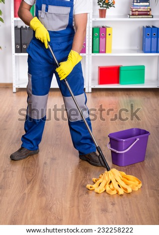 Young man in blue uniform is cleaning the floor. - stock photo