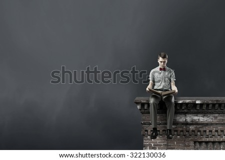 Young man in bow tie sitting with book in hands - stock photo