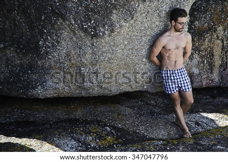 Young man in boxer shorts leaning against rock - stock photo