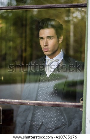 Young man in bridal suit looking through the window - stock photo