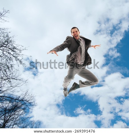Young man in business clothes  jumping in the air