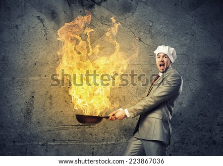 Young man in business suit and cook hat holding pan - stock photo