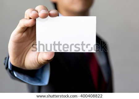 Young man in business suit holding white blank business card. Business name card presenting