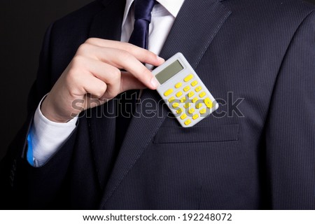 young man in business suit putting calculator into pocket - stock photo
