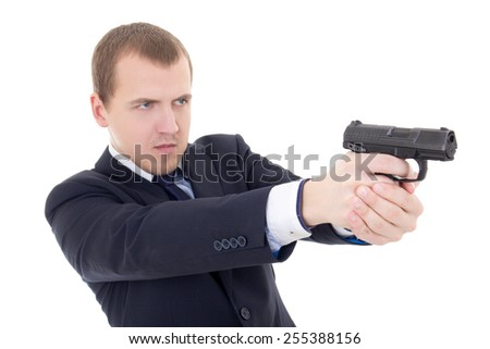 young man in business suit shooting with gun isolated on white background - stock photo