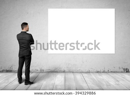 Young man in business suit, standing front of concrete wall with white blank board on it. - stock photo