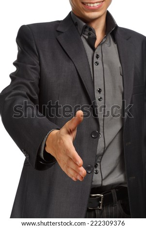 Young man in business suit stretching his hand for handshake isolated on white background. Focus on hand - stock photo