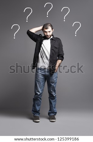 young man in casual clothes has a lot of questions - stock photo