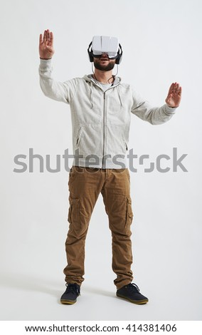 Young man in casual clothes trying to push something wearing virtual reality glasses - stock photo