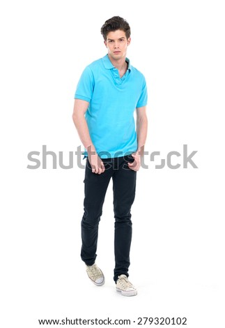 Young man in casual clothes walking in studio over white background.
