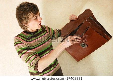Young man in casual clothes with empty briefcase