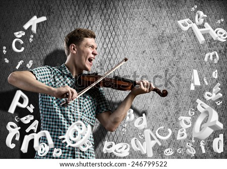 Young man in casual on cement background playing violin - stock photo
