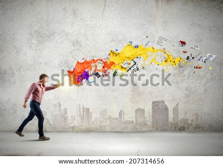 Young man in casual throwing colorful paint splashes - stock photo