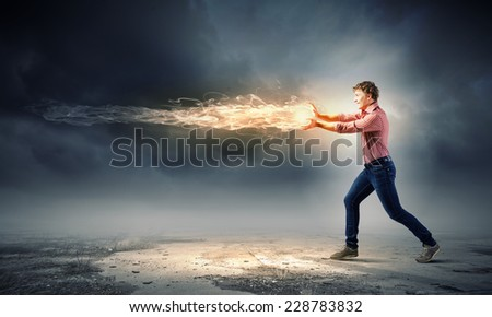 Young man in casual throwing magic fire balls - stock photo