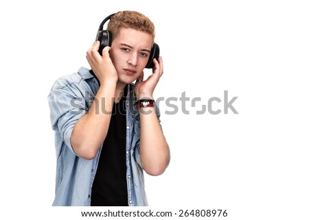 Young man in casual, trendy clothing listening to music and holding wireless headphones with eyes opened and a cool expression, isolated on white - stock photo