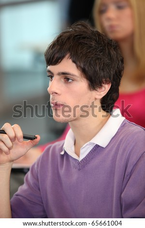 Young man in classroom at university - stock photo