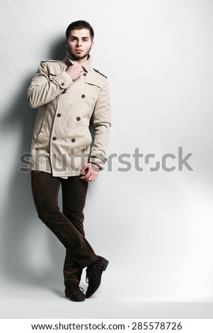 Young man in coat on gray background - stock photo