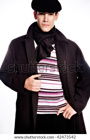 young man in coat wearing beret, studio on white - stock photo