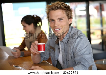 Young man in coffee shop wonnected on smartphone - stock photo