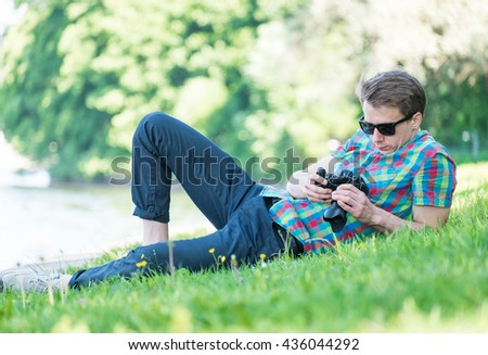 Young man in colorful shirt with digital camera resting on green fresh grass in park
