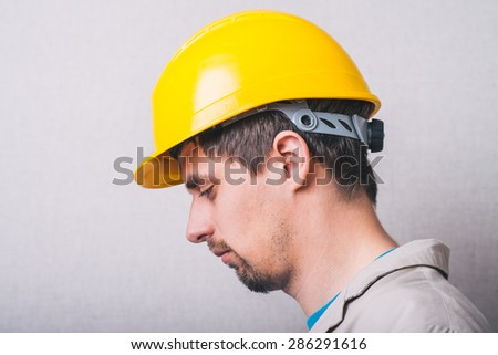 Young man in construction helmet having depression