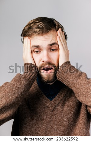 young man in despair and holding hands behind his head - stock photo