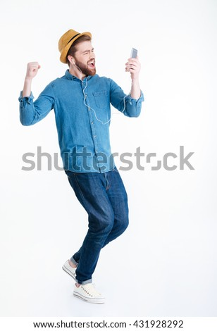Young man in earphones dancing holding smart phone isolated on the white background - stock photo
