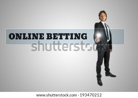 Young man in elegant suit activating Online betting button on virtual screen. - stock photo