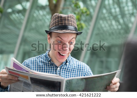 Young man in fashionable hat surprised  of newspaper news, or just win in lottery - stock photo